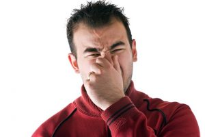 man holds or pinches his nose