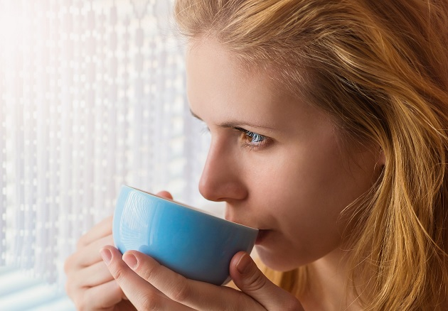 woman sipping coffee from her cup